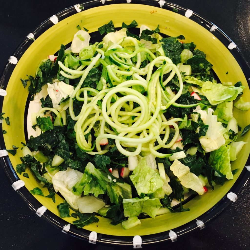 Green salad with zucchini noodle topping